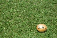 金子在绿草的复活节彩蛋 免版税图库摄影