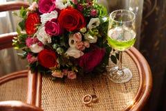 金子婚戒,一杯香槟,在桌上的花束 库存图片