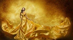 金子时装模特儿礼服,妇女金黄丝绸褂子流动的织品 库存照片