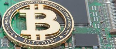 金子特写镜头咬住了硬币、计算机电路板与bitcoin处理器和微集成电路 电子货币,互联网财务ryp 免版税库存图片