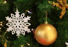 金子球形的圣诞节装饰品的特写镜头与被弄脏的白色雪花装饰品的 库存照片
