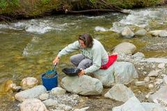 金子的妇女摇摄在云杉的小河, BC 免版税库存图片