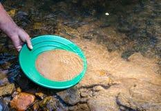 金子的摇摄在矿物富有的小河 免版税库存图片
