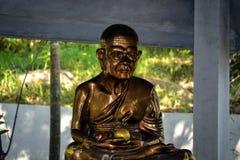 金子菩萨用在佛教寺庙的苹果在一个小泰国村庄的密林 库存图片