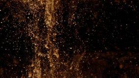 金子闪烁进入水有黑背景,对底部的沉淀物并且溶化 股票视频