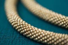 金子颜色一条被编织的项链的片段  图库摄影