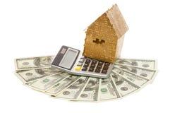 金子颜色的家在计算器和美元的 免版税库存照片