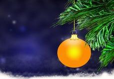 金子黄色圣诞节球背景蓝色雪盘旋 库存图片