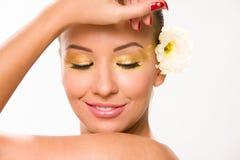 金子组成 有白花的布朗光滑头发美丽的妇女在接近看的面孔的手上下来 库存图片