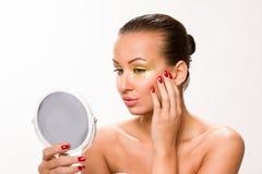 金子组成 看镜子的布朗光滑头发美丽的妇女 免版税库存图片