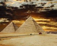 金字塔在日落的背景的,开罗,埃及吉萨棉 免版税库存照片