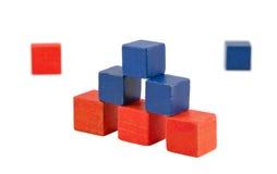 金字塔由木红色蓝色颜色玩具砖做成 免版税库存图片