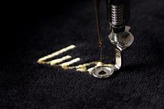 金字法& x22刺绣; luxury& x22;在与刺绣机器的黑柔软光滑的织品 免版税库存照片