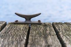 金属停泊系船柱在一座木码头桥梁的在海,警察 免版税库存照片