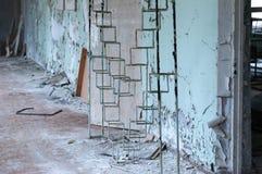 金属分开软的焦点在被毁坏的蓝色墙壁前面的在被放弃的学校在离开的Pripyt镇 免版税库存图片