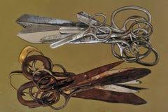 金属剪刀两堆是不同的大小:从老生锈的剪刀下面,从上面是新的发光的银色剪刀 免版税图库摄影