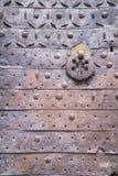 金属化与一个伪造的样式的铁锈门与敲的圆环 免版税库存照片