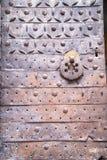 金属化与一个伪造的样式的铁锈门与敲的圆环 库存照片