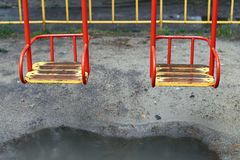 金属化与一个木位子的摇摆在一个孩子操场在与水坑的一个雨天在它下 免版税图库摄影