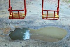 金属化与一个木位子的摇摆在一个孩子操场在与水坑的一个雨天在它下 免版税库存图片