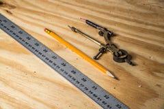 金属化与分度器和铅笔的统治者在木头 免版税库存图片