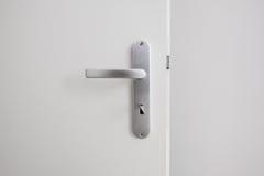 金属化与钥匙的门把手在白色门 库存图片