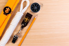金属化口哨、侦察员围巾、绳索、铅笔和指南针在木背景 免版税库存图片