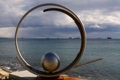 金属化圆环和球形的纪念碑在海的背景有船的 免版税库存照片