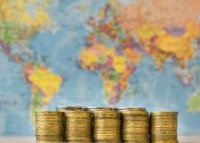 金属化在世界的背景地图的硬币 免版税图库摄影