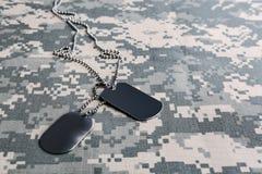 金属化在伪装背景的军事ID标记 库存照片