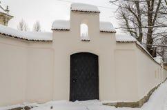 金属化在修道院的防御篱芭的黑门撒布与雪在一个冬日 免版税库存照片