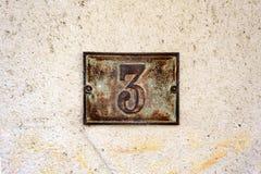 金属化在涂灰泥的墙壁上的房子号码3 免版税库存照片