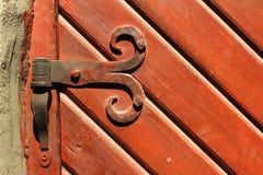 金属化在老红色被绘的木门的铰链 库存图片