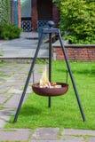 金属化在草的三脚架壁炉与灼烧的木柴 免版税库存图片