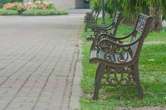 金属化在绿草的钢古板的长凳椅子 免版税图库摄影