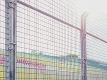 金属化墙壁篱芭在前边椅子在体育体育场的有清楚的s的 库存照片