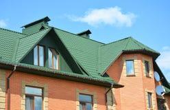 金属化屋顶有顶楼、雨天沟和屋顶问题范围的房子建筑 免版税库存图片