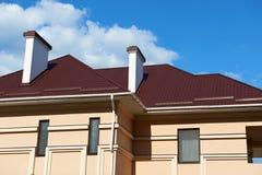 金属化新的私有房子屋顶和墙壁,有烟囱和透气的在天空背景,建筑概念,家庭关于 库存照片