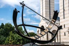 金属化日规或太阳时钟有罗马数字的在公园和大厦在背景中 库存照片