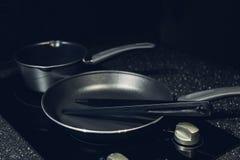 金属化有不粘锅的涂层的黑煎锅在电火炉 免版税库存照片