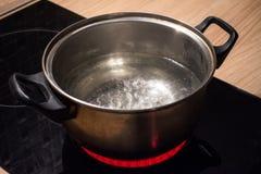 金属化有开水的平底锅在电磁炉炽热板材 图库摄影