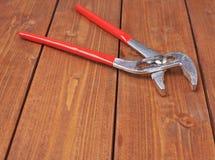 金属化有红色把柄的水管工板钳木表面上 免版税库存照片