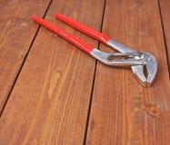 金属化有红色把柄的水管工板钳木表面上 库存图片