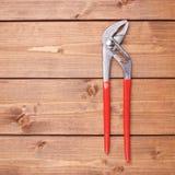金属化有红色把柄的水管工板钳木表面上 库存照片