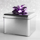 金属化有紫色弓的礼物盒在白色闪烁背景 免版税库存图片