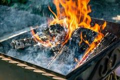 金属化格栅,伪造,手工制造,与样式 在木头的热的火与烤肉和烤产品的烟 免版税库存图片