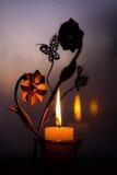 金属化烛台以与蝴蝶的花的形式与一个灼烧的蜡烛 免版税库存照片