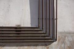 金属化煤气管在水泥都市墙壁 免版税库存照片