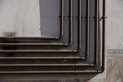 金属化煤气管在水泥都市墙壁 库存图片