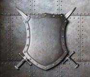 金属化盾和两把横渡的剑在装甲 免版税库存照片